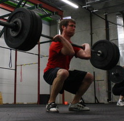 Man lifting weights from squatting position