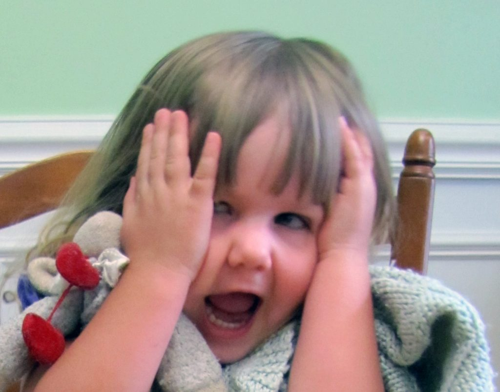 Little girl, squishing her face and yelling - looking exasperated