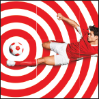 Man in red shirt and white shorts kicking a red soccer ball into the center of concentric red rings
