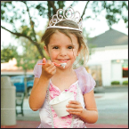 Little girl in a princess dress and crown eating ice cream